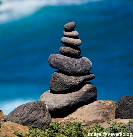 a spa looking stack of river rocks that are charcoal gray with a blue ocean backdrop