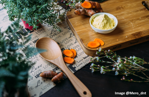 wooden spoon resting on a table with fresh herbs and turmeric slices around it and a wooden cutting board