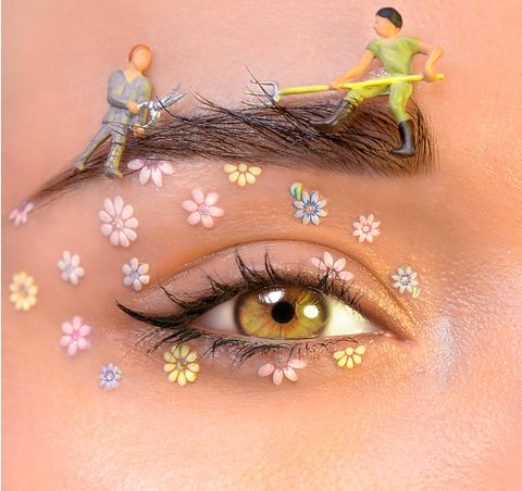 woman with green eyes looking directly ahead and art on her eyelids of flowers and mini male figures grooming her eyebrows