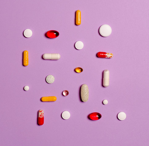 an assortment of different colors and shapes of pills against a purple background