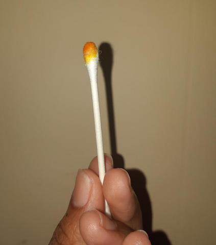 white q tip with an orange liquid on the tip