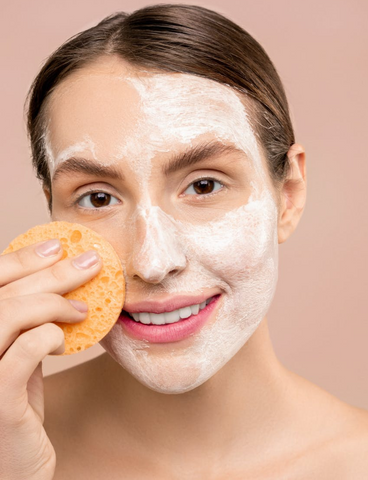 woman smiling with hair pulled back and a sponge in her hand with a white cream mask on her face
