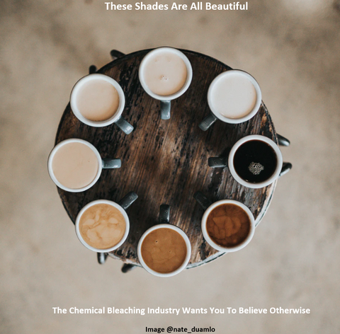 round wooden table with an overhead view of cups of coffee and cream with different shades