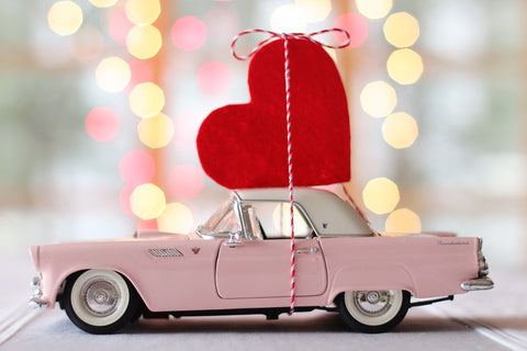 Pink thunderbird vintage car toy with red felt heart attached to the top with a ribbon
