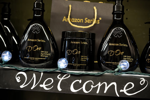 Amazon D'Oro 24K Gold Shampoo, Conditioner, and Masque sit on the shelf at Fine Edge Beauty & Barber Supply in Vancouver, BC with a Welcome sign beneath