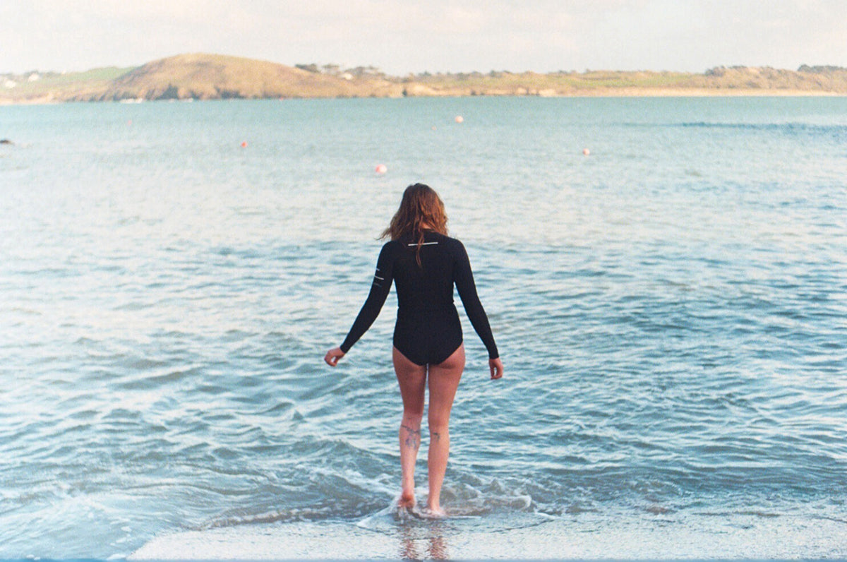 Lottie Lewis entering the cold waters of Cornwall wearing the Finisterre Yulex 2e swimsuit