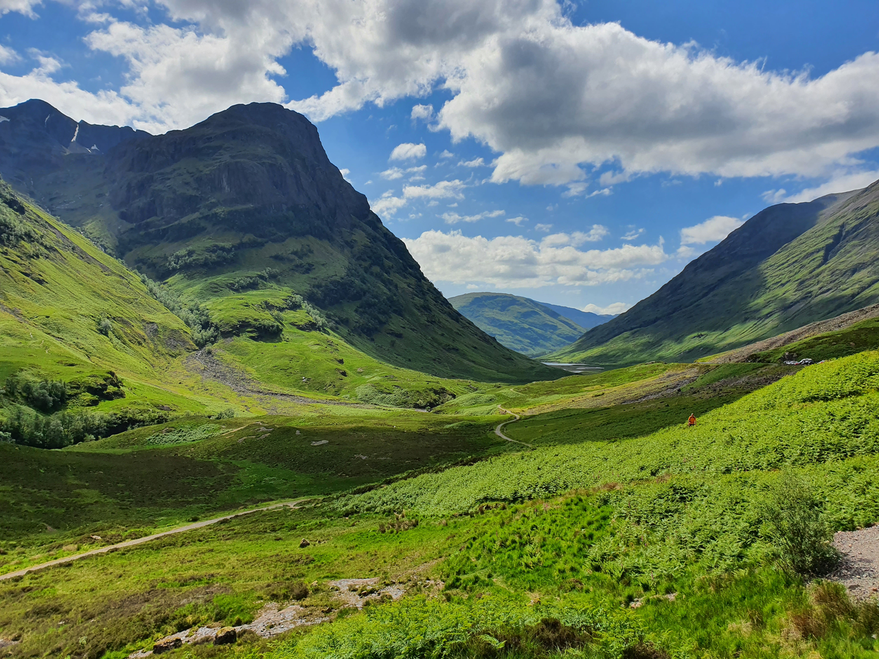 Scottish highlands with green shrubbery and cloudy blue sky