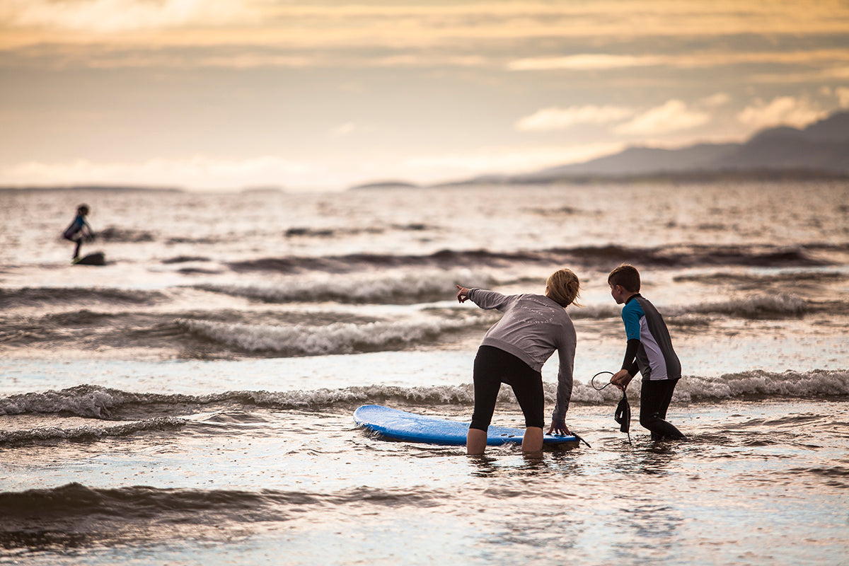 Young boy and surf therapist working together at the beach