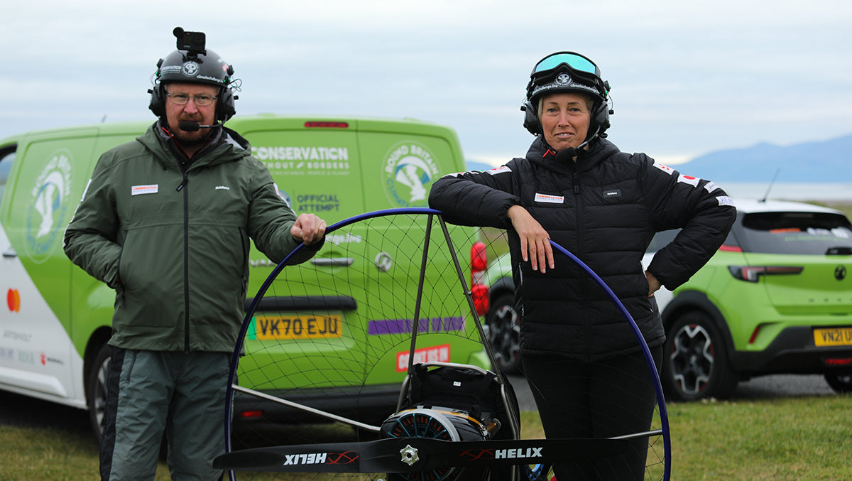 Sacha Dench and a support crew member pose with their paramotor before the flight