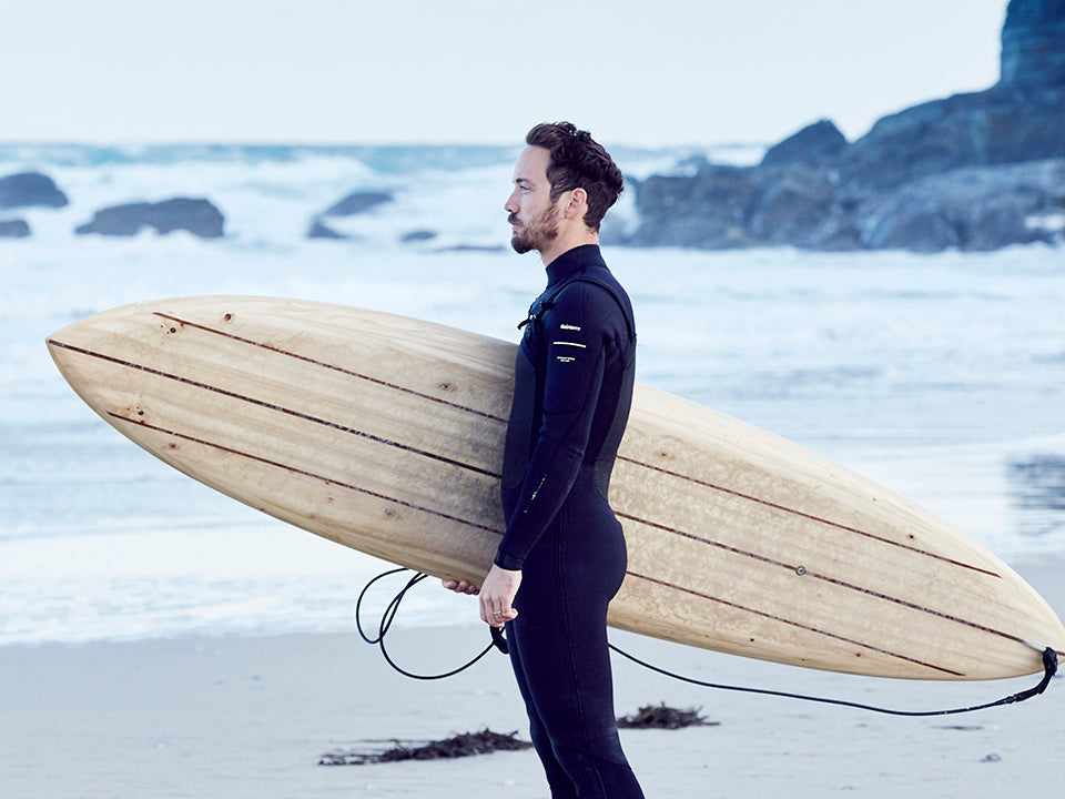 James Otter with one of his wooden boards preparing to paddle out for a surf