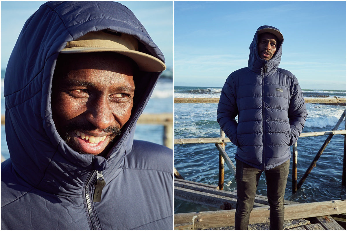 Finisterre Ambassador Apish Tshetsha wearing the Nebulas Jacket by ocean
