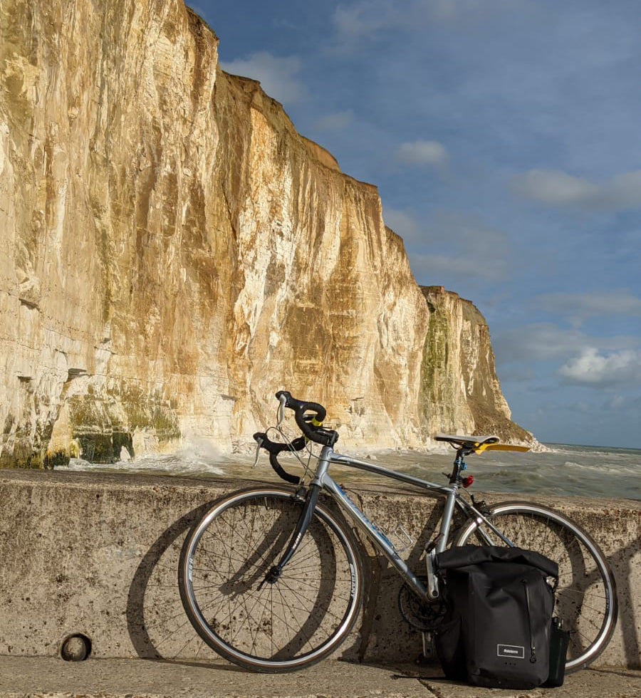 A Bicycle and Finisterre bag resting by the wall in front of white cliffs.