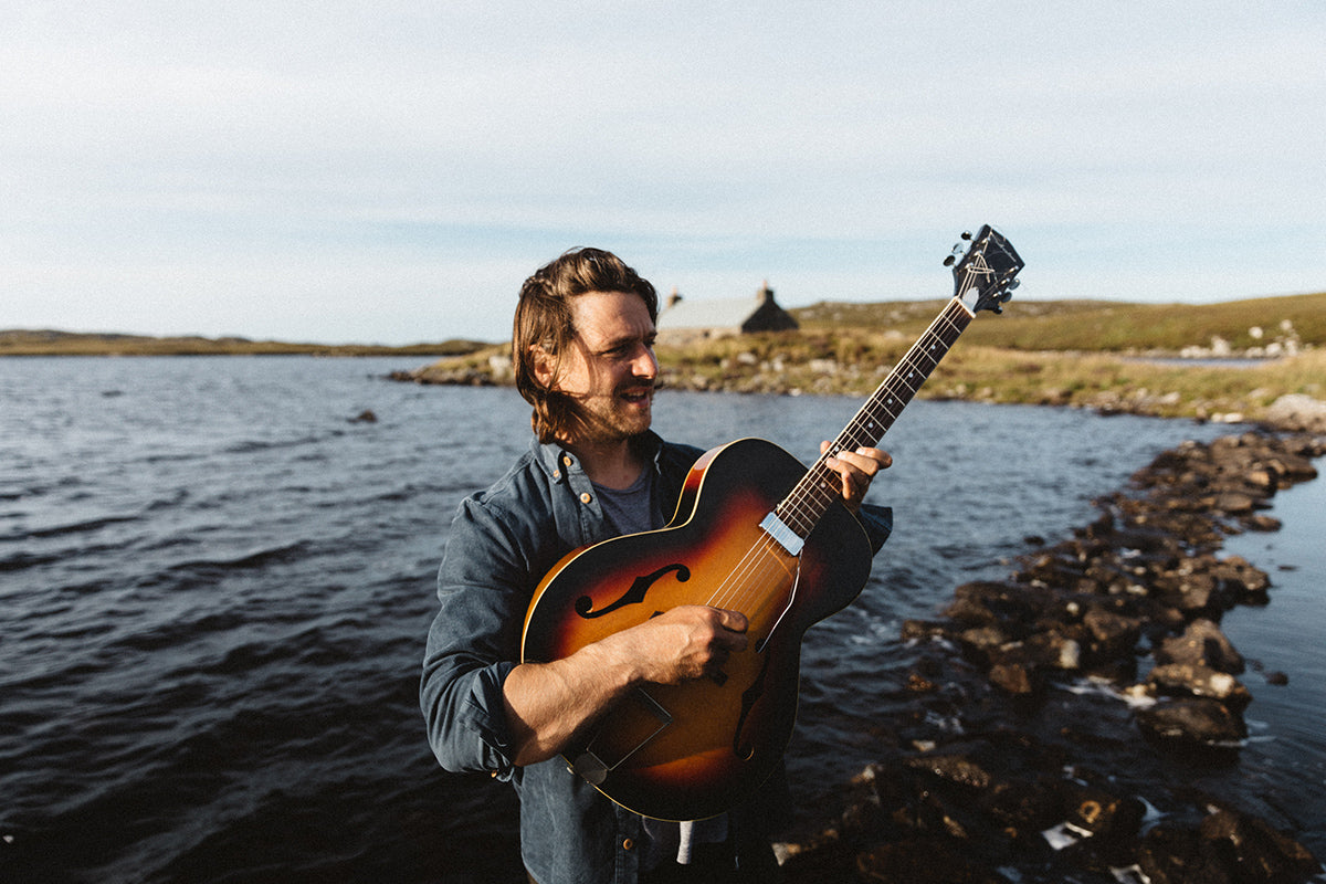 Colin Macleod playing his guitar on the shoreline wearing the Finisterre Leonard shirt