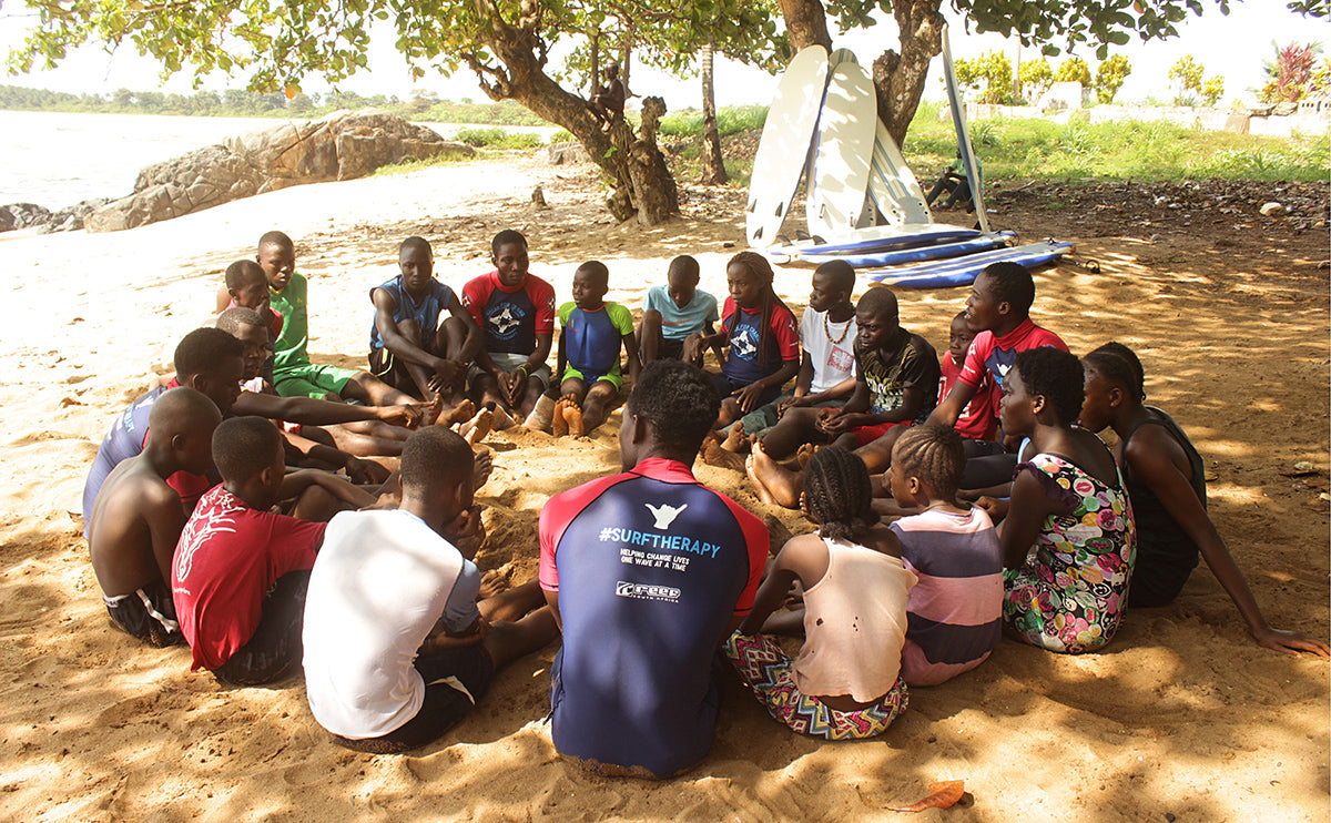 A group of Wave Alliance participants sit in a circle under shade to talk before taking to the waves