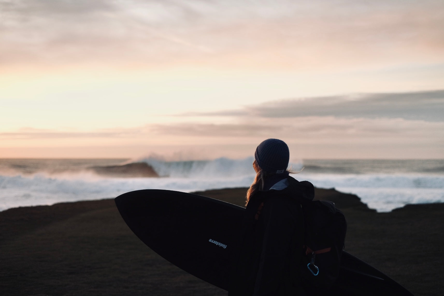 Eaaskey Britton looks out to sea with surfboard in hand - Oceanographic 18