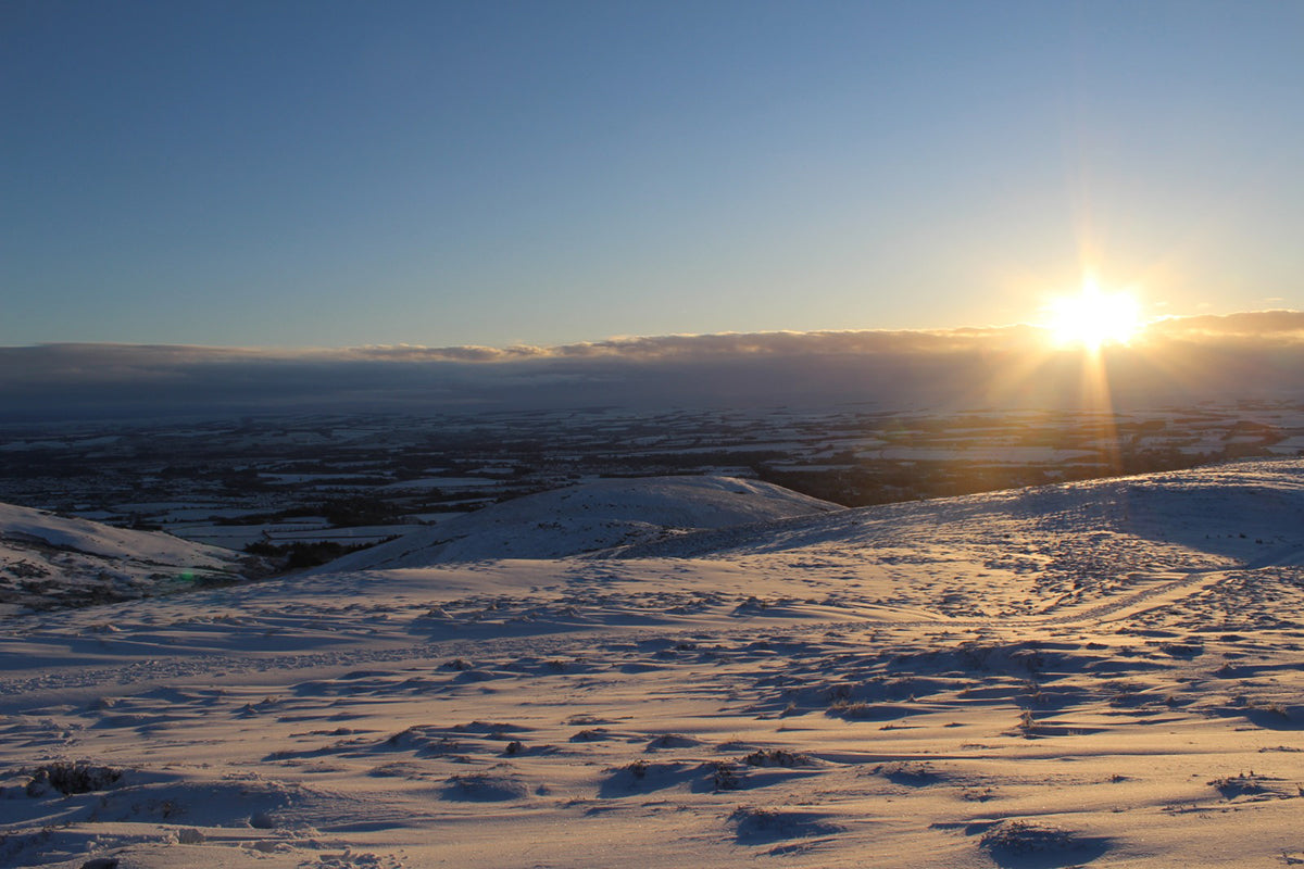 The sun sets over a snow covered scene in the Pentland Hills