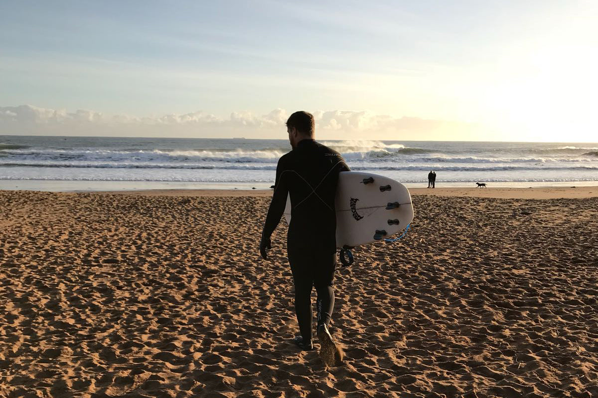 Edinburgh store manager Jack walking across the beach with surfboard in hand