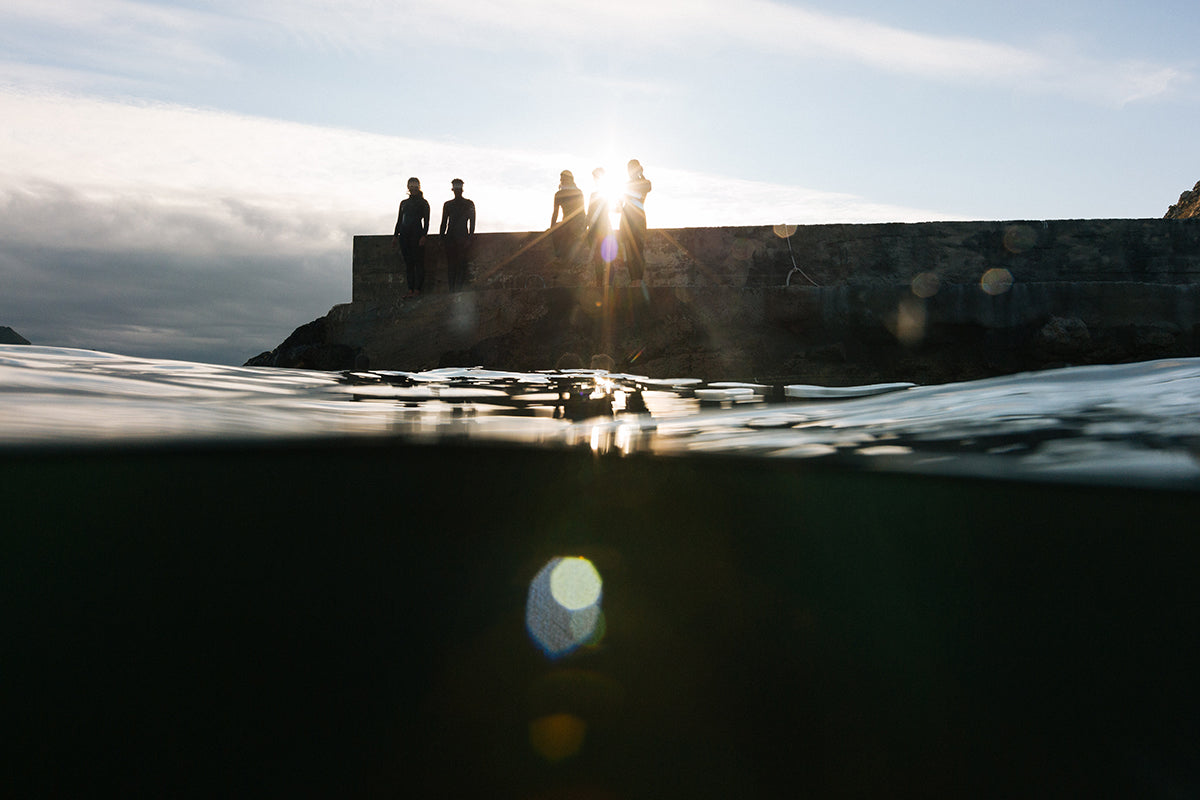 Sea goers on a harbour wall getting ready to dive in