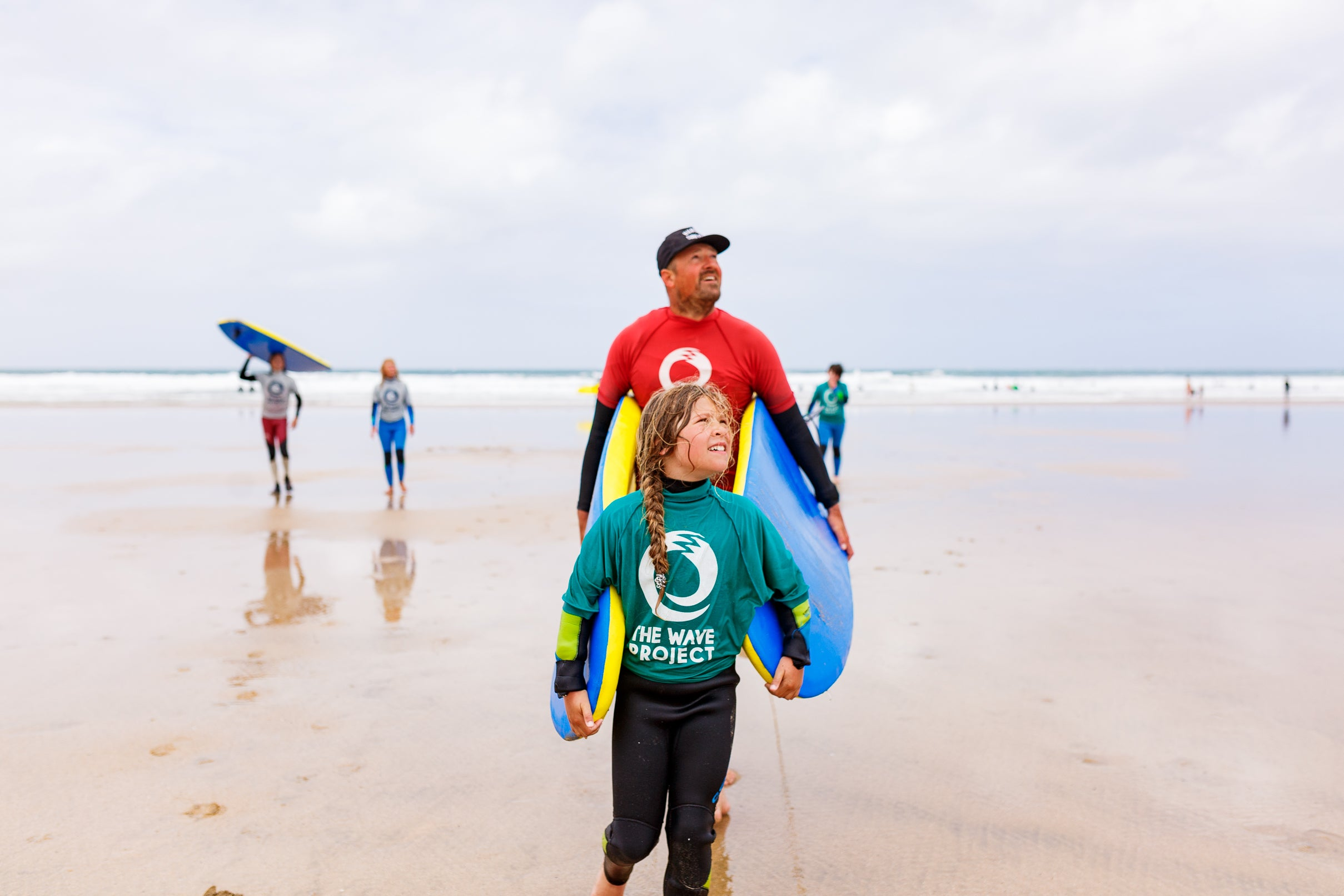 Sam Lamiroy walking a wave project participant up the beach with boards in tow