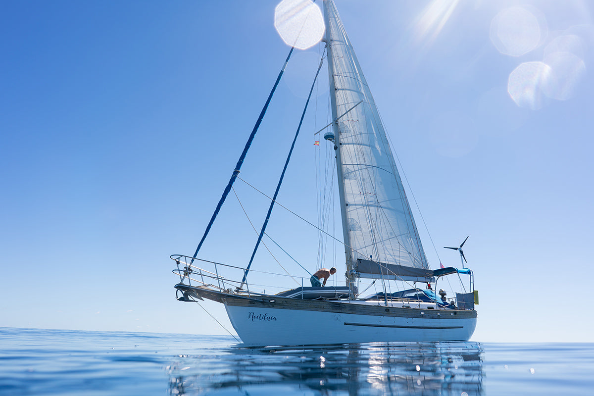 The Author's vessel, Noctiluca, sitting in calm blue waters