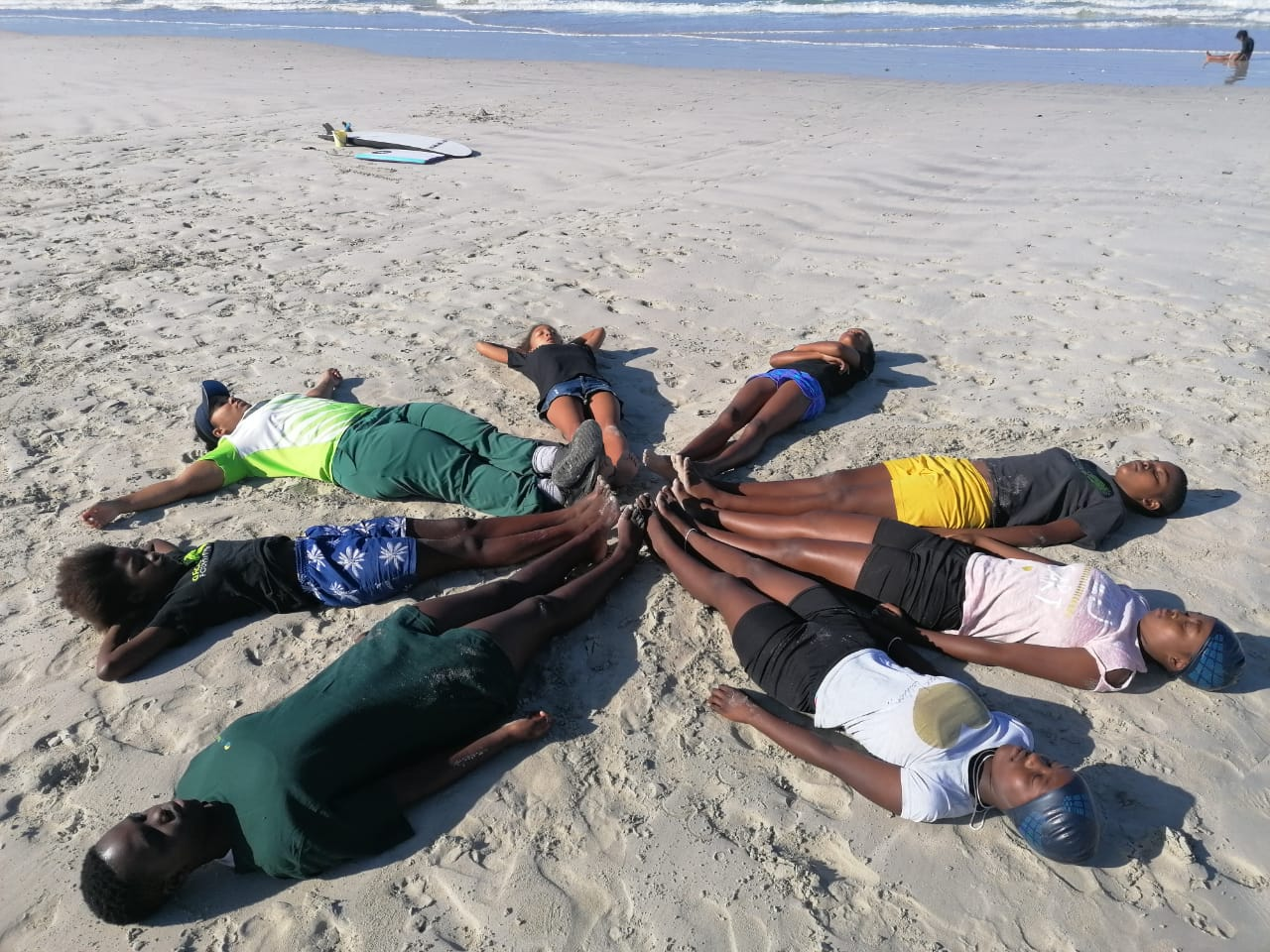 Girls lying in a circle on the beach as part of Surf Therapy with Wave Alliance