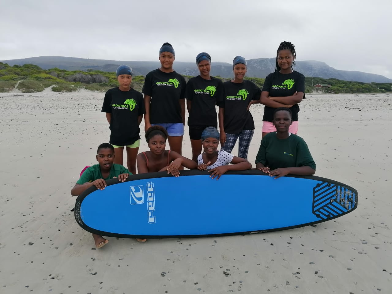 Group of girls in grootos foundation tshirts standing by a surfboard on the beach