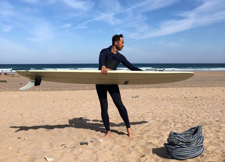 Paul waxes up his board ready to head out for a surf