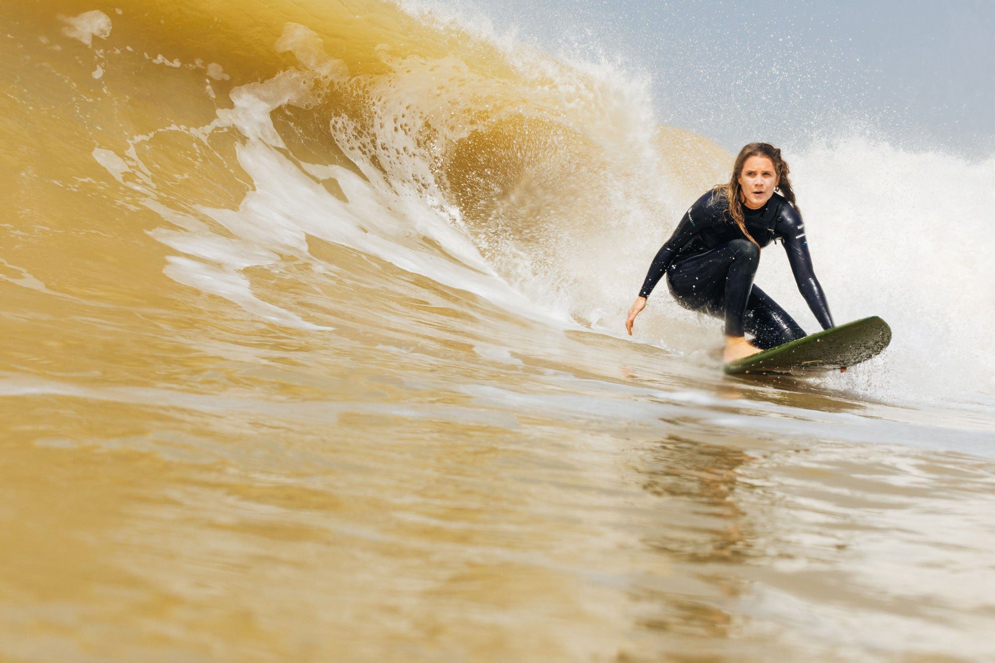 Head-of-Finisterre-repairs-Amy-Brock-Morgan-grabbing-the-rail-as-she-turns-onto-the-face-of-a-wave-in-Senegal