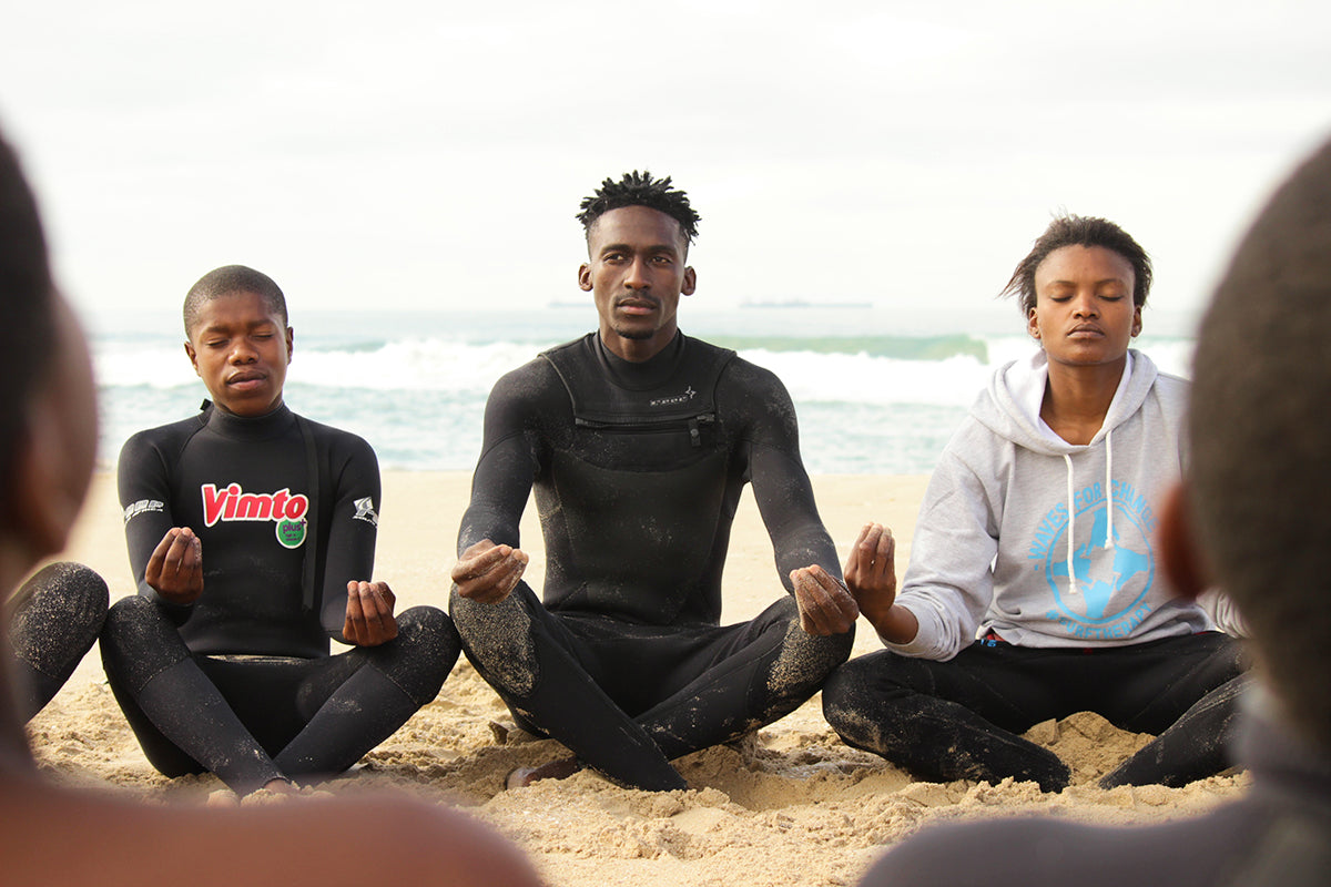 Finisterre Ambassador Apish Tshetsha sits on the beach meditating with a group of kids as part of the surf therapy session.