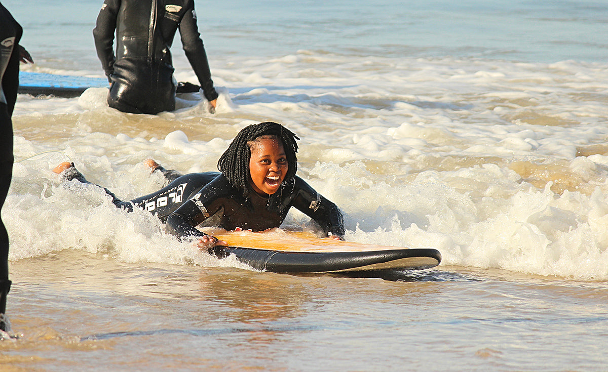 A young Waves for Change surfer smiling widely as they catch a wave into the shore
