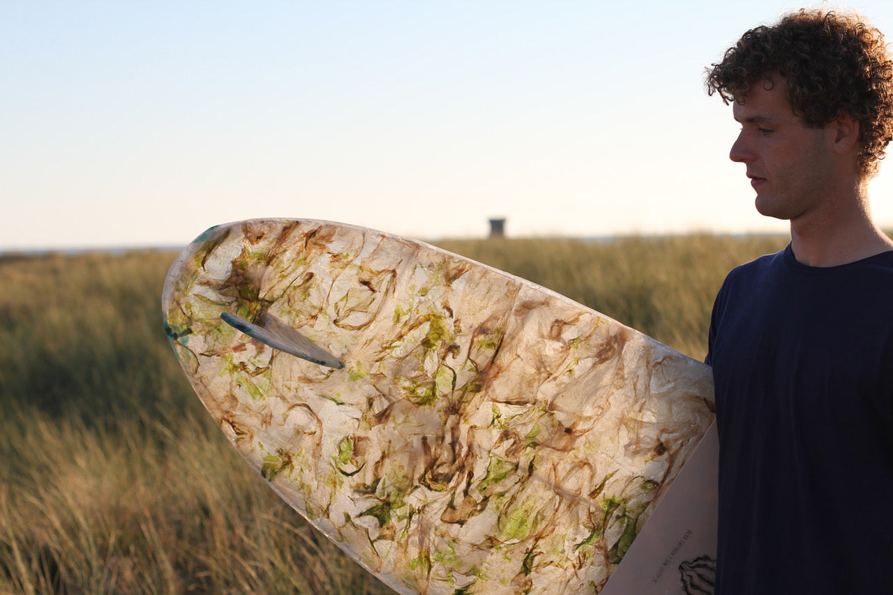 Charlie Cadin with his first surfboard shaped on sea lettuce