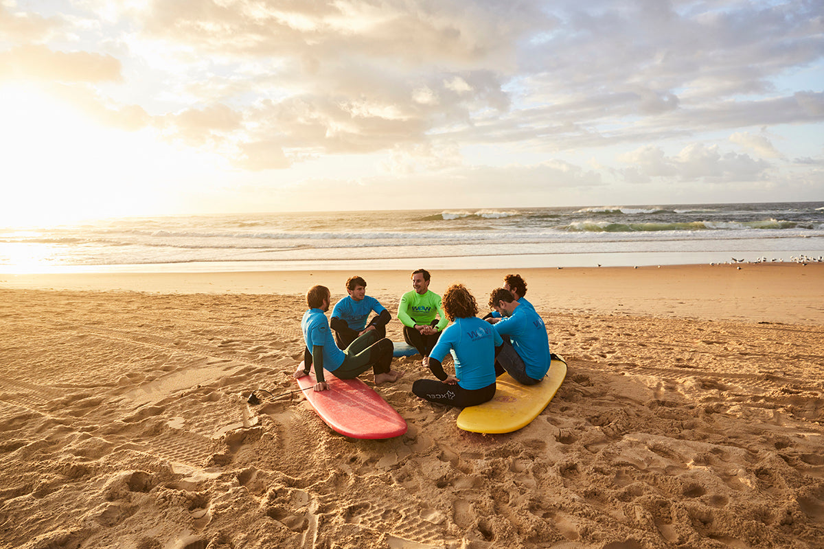 A surf therapy session group talk in a circle before their surf