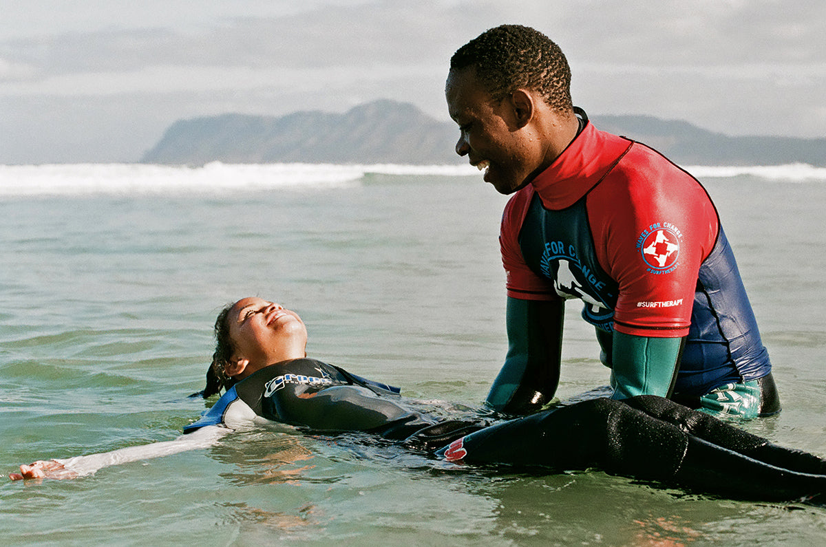 A volunteer in South Africa helps a young participant get comfortable in the ocean