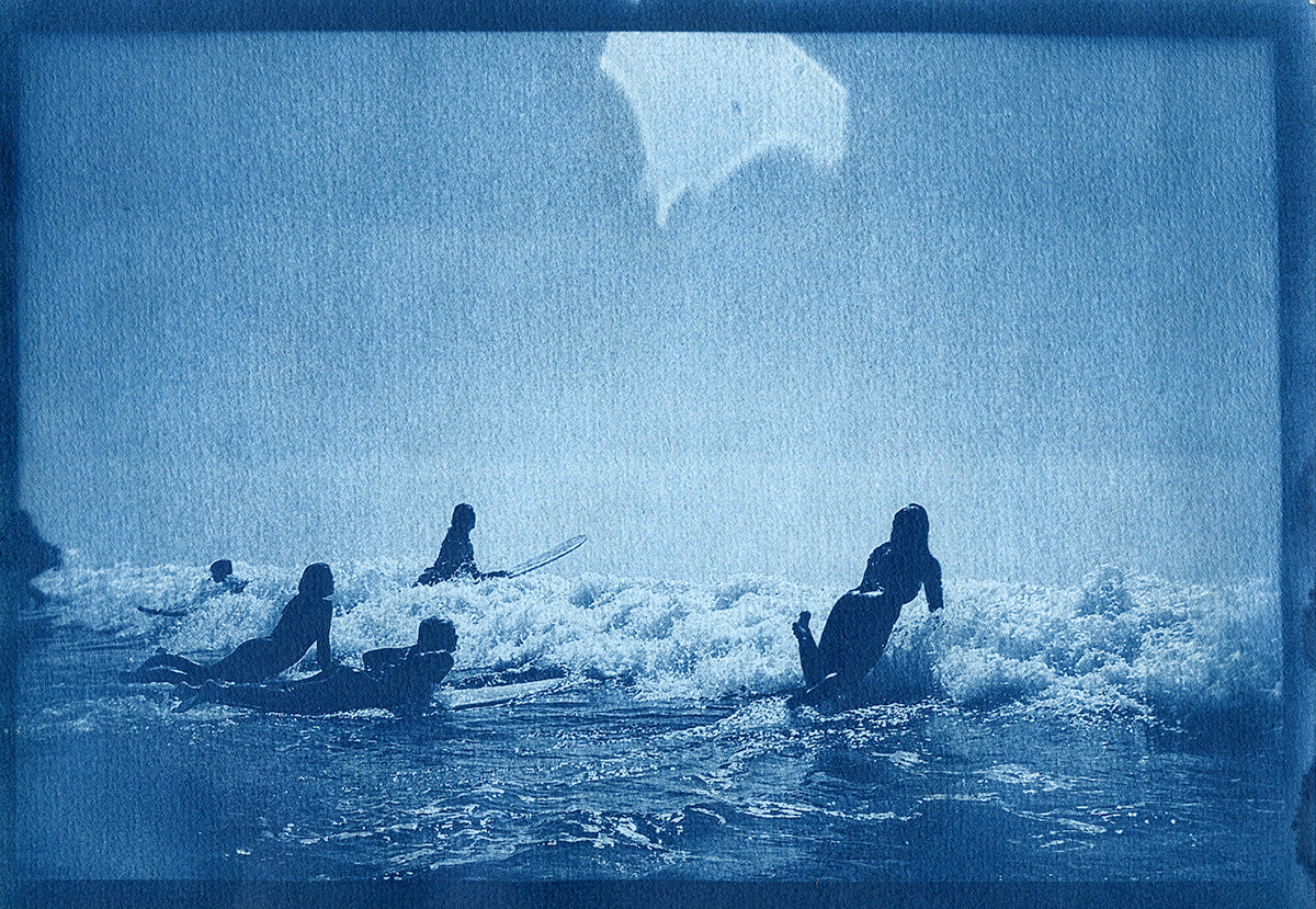 Cyanotype image of surfers pushing through a broken wave by Ines Ambrosio