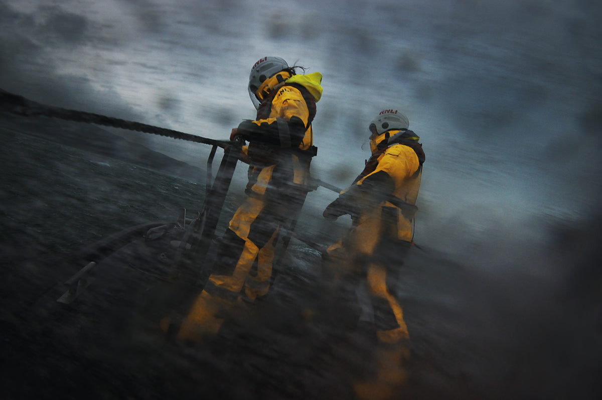Two RNLI volunteers stand on deck against a ferociously stormy sea