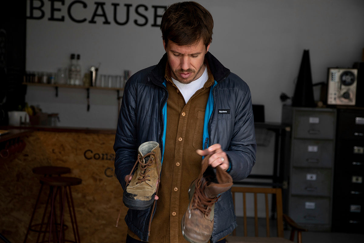 Mat Arney holding his old palladium boots and wearing a Finisterre Etobicoke jacket