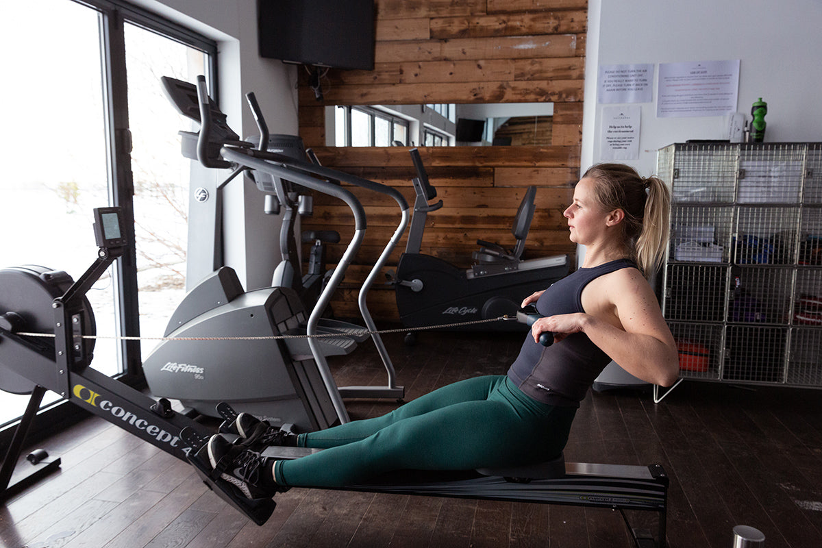 Bella hits the rowing machine in the gym wearing Finisterre Zonda active top and Vela bamboo leggings