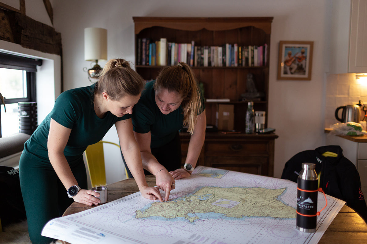 Bella and Mary closely examining the maps and charts that will guide their crossing