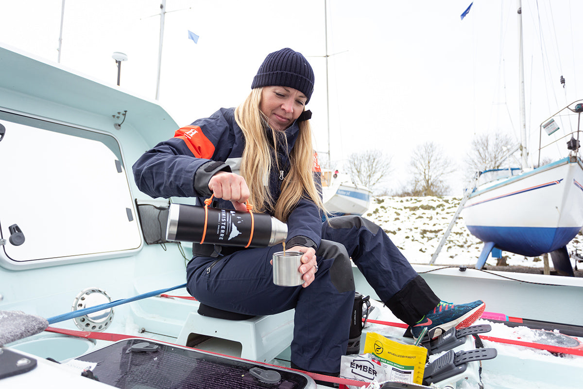 Purusha sits aboard the boat Fenris and pours a cup of tea from her Finisterre insulated flask