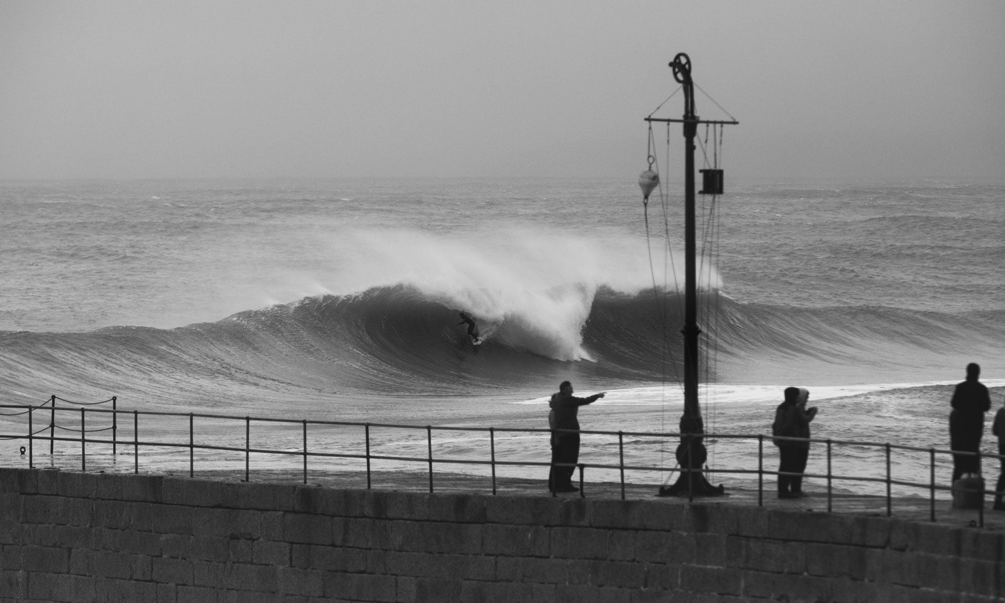Onlookers watch from the harbour as an unknown surfer navigates a heavy barrel - imagecredit JackJohns