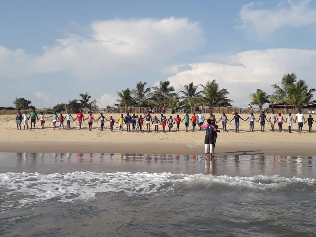 Wave Alliance participants in Liberia link hands on the tideline of a beach