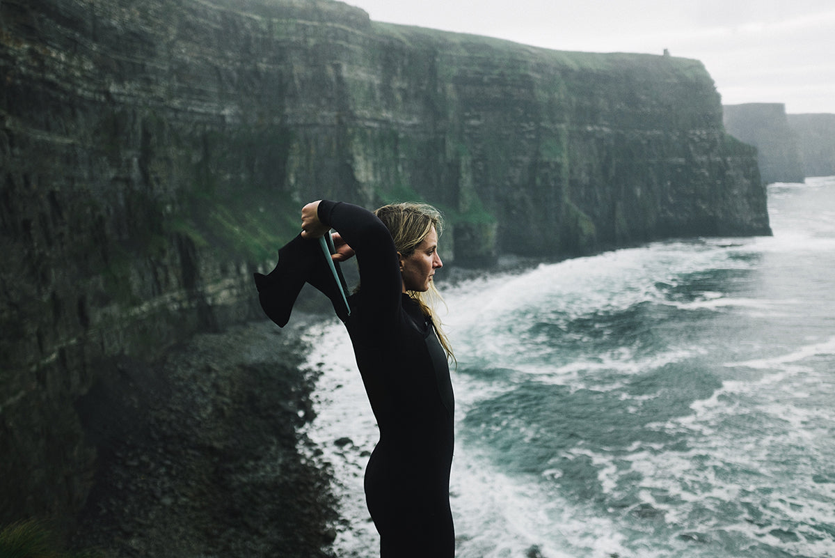 Surfer, scientist and Finisterre Ambassador Easkey Britton pulls on her hooded wetsuit at the Cliffs of Moher.