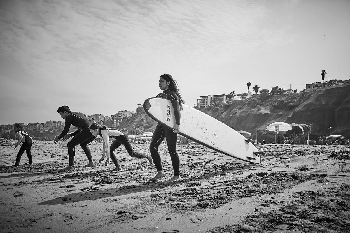 Alto Peru Wave Alliance participants head to the water with their surfboards