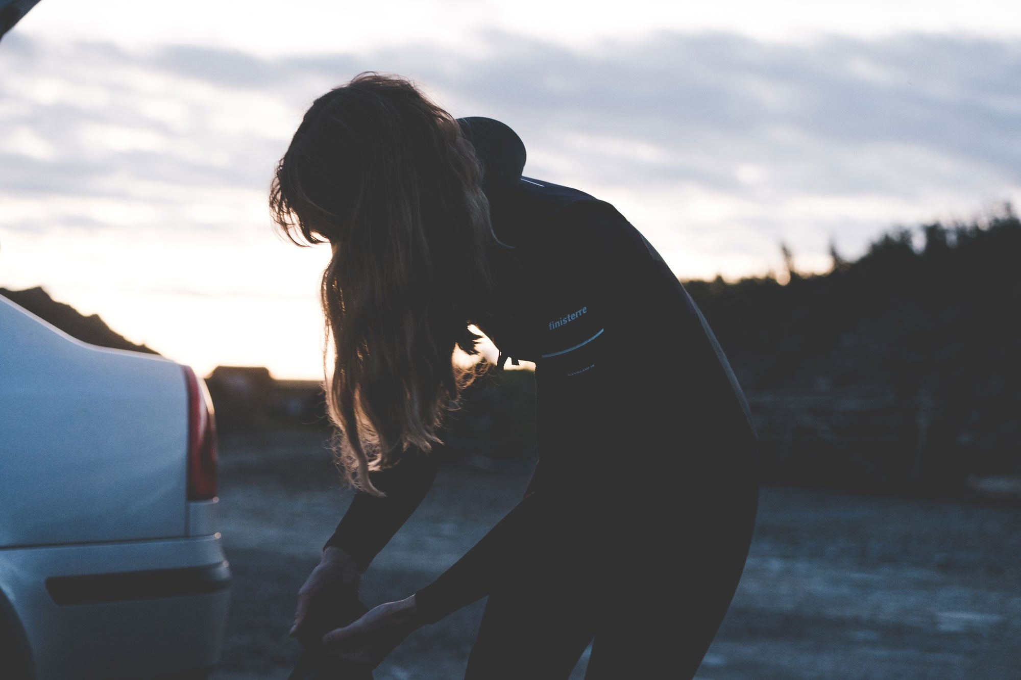 Sally McGee getting changed into her Finisterre wetsuit on a dark morning - Image Credit Tom Bing