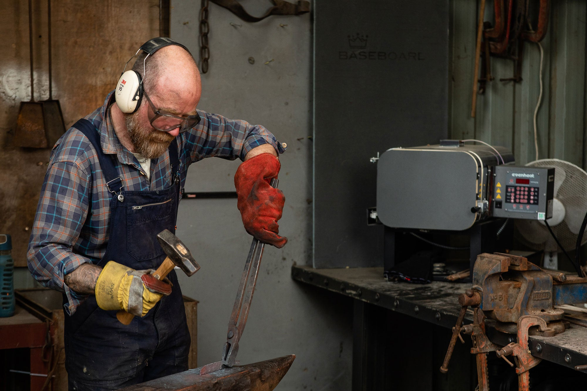 Sam Gleeson hammering steel in his workshop