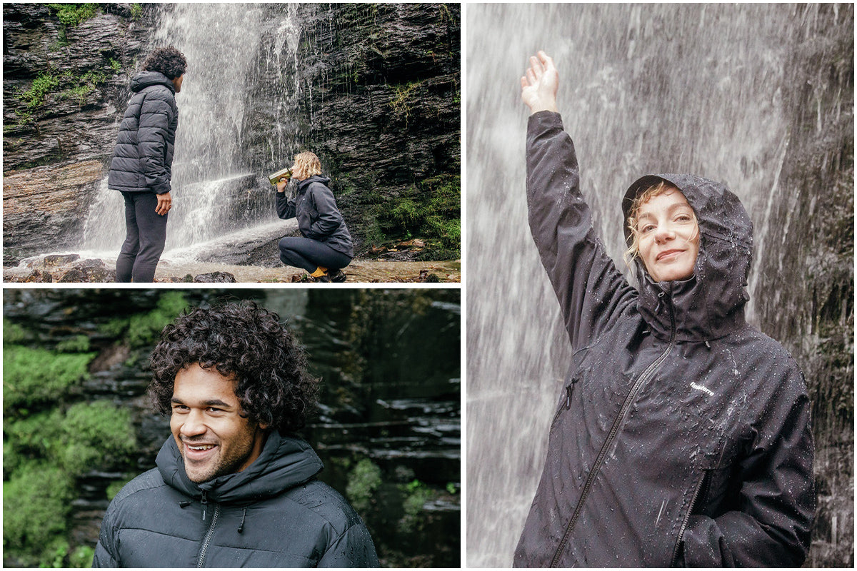 Young woman and man wearing Finisterre jackets by a waterfall.
