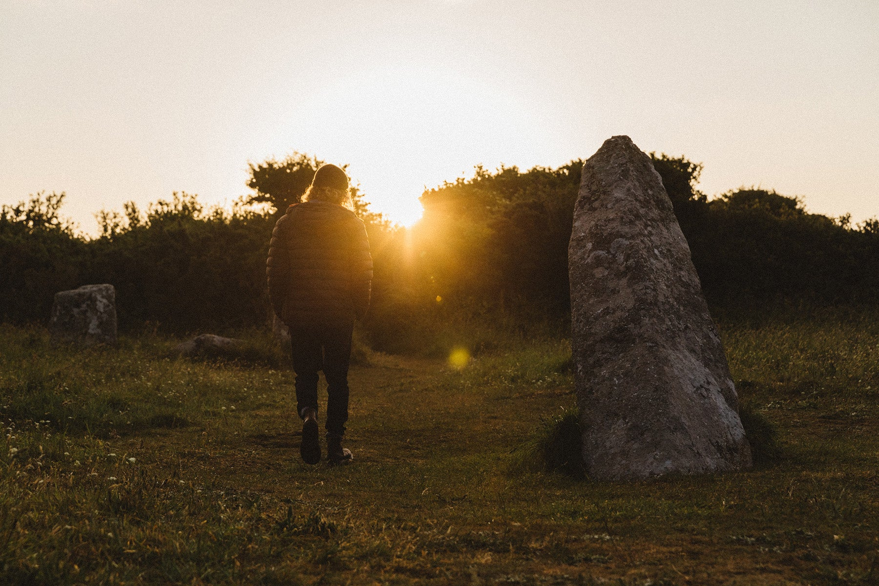 Pete Geall next to the central standing stone at Boscawen-ûn stone circle as the sun peeks over the horizon