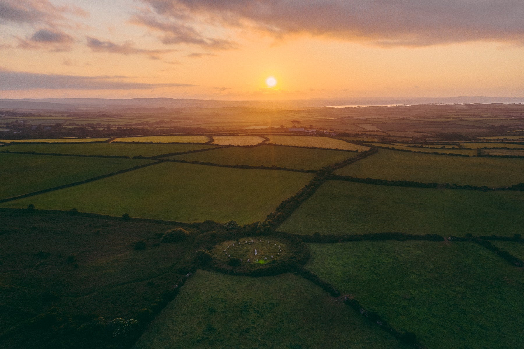 The sun rising  above the landscape of West Penwith and the stone circle