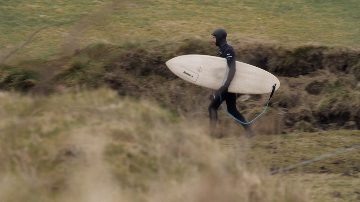 Fergal Smith wearing a 5mm Finisterre Hooded Wetsuit, running to the surf