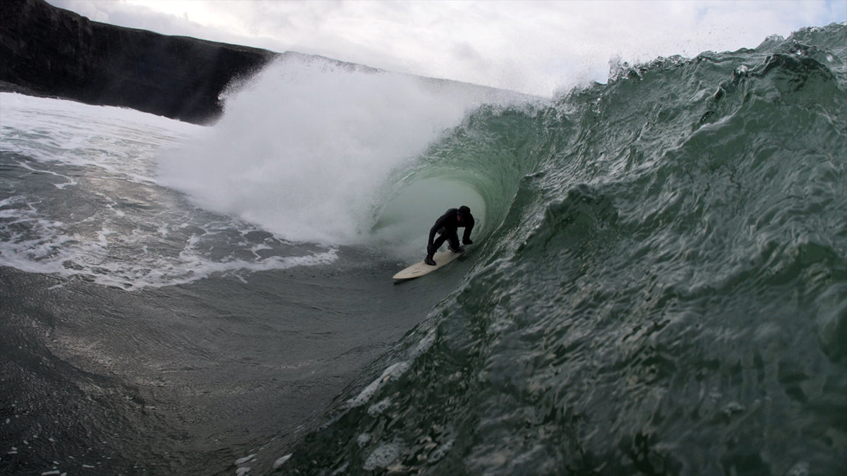 Fergal Smith barrel riding a slabbing left in a Finisterre Wetsuit